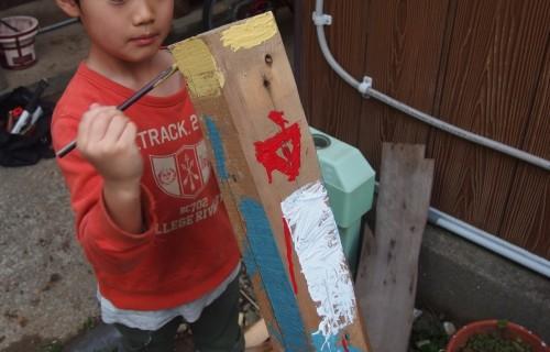 ペンキで絵を書いてくれている息子。 ななめになっている節穴2つが目なんだそうです。